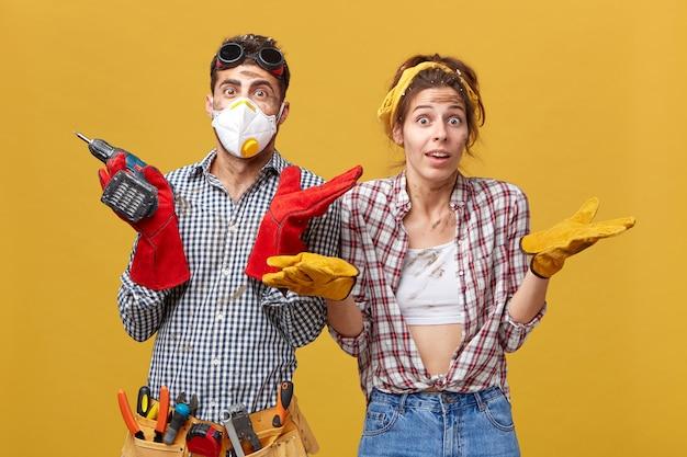 男性と女性の肉体労働者は、何から始めればいいのかわからない怪しげな表情で肩をすくめます。いくつかの疑問や不確実性を持つ掘削機を保持している若い男 無料写真