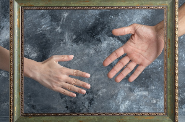 남성과 여성의 그림 프레임 중간에 손을 보여주는. 무료 사진