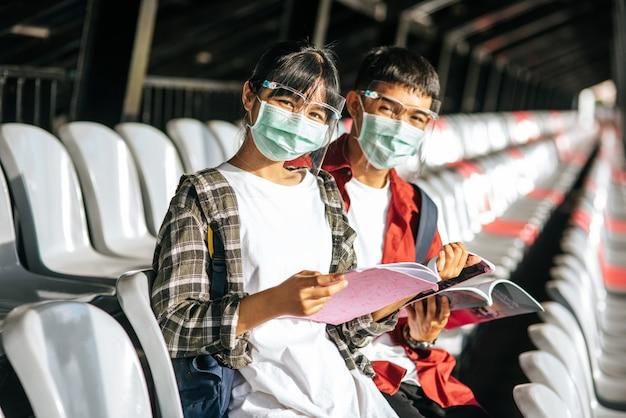 男性と女性の学生はマスクを着用し、フィールドチェアに座って読む 無料写真