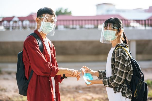 男性と女性の学生はマスクを着用し、ジェルを絞って手を洗います。 無料写真
