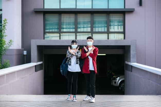男性と女性の学生はマスクを着用し、大学の前に立っています。 無料写真