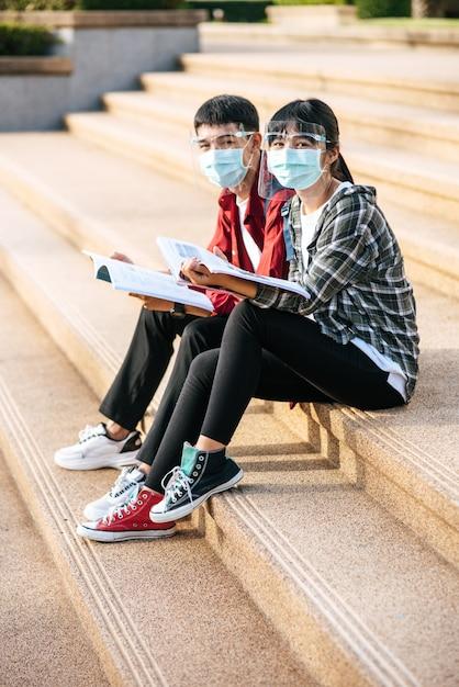 マスクをした男性と女性の学生が座って階段で本を読む 無料写真