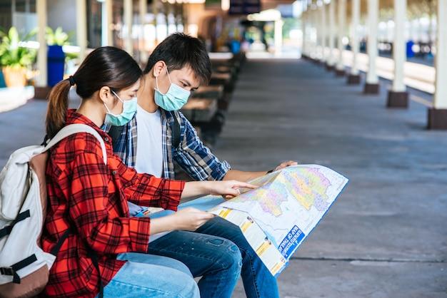 Туристы мужского и женского пола смотрят на карту возле железной дороги. Бесплатные Фотографии