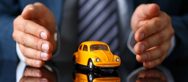 Male arm in suit and tie cover yellow toy car Premium Photo