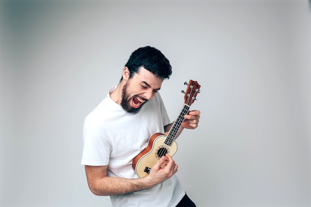 Male artist play on ukulele and singing. screaming out loud. practicing in playing on small guitar. have fun Premium Photo