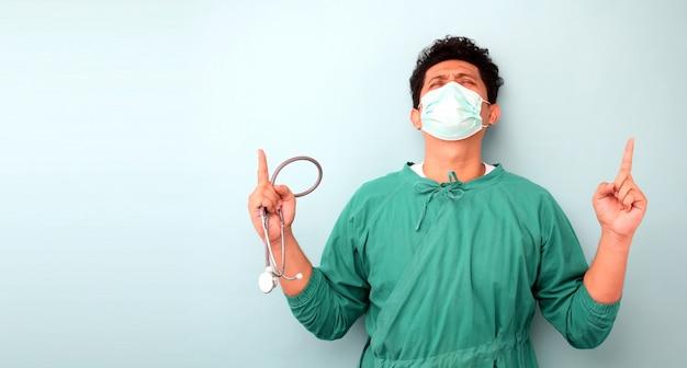 男性のアジアの外科医の医師、外科医が青い壁の上の外科医のマスクを着て聴診器を見せて、見上げると指と上げられた腕で指していると驚いて感じる。 Premium写真