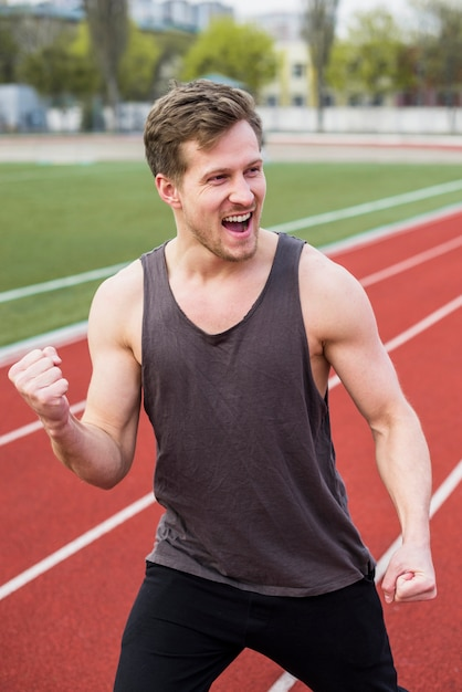 Male athlete celebrating his victory on race track Free Photo