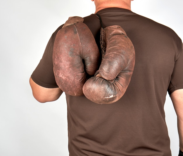 Male athlete holds a pair of very old vintage boxing gloves Premium Photo