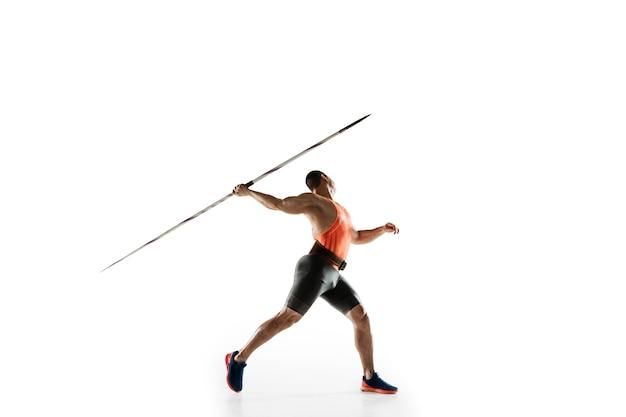 白いスタジオでやり投げの練習をしている男性アスリート。 無料写真