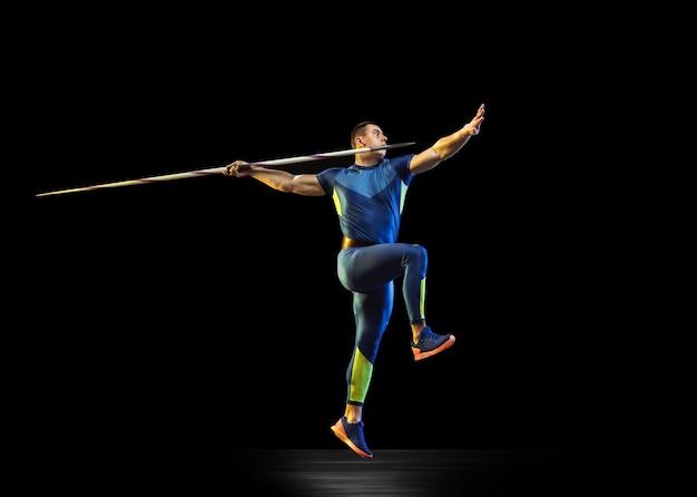 Atleta maschio che pratica nel lancio del giavellotto nel buio Foto Gratuite