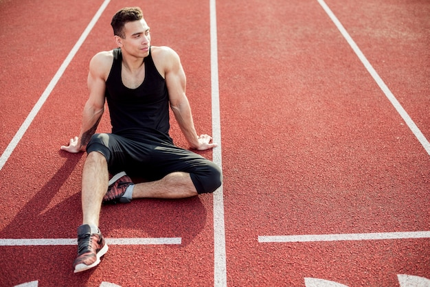 Male athlete relaxing on red race track Free Photo