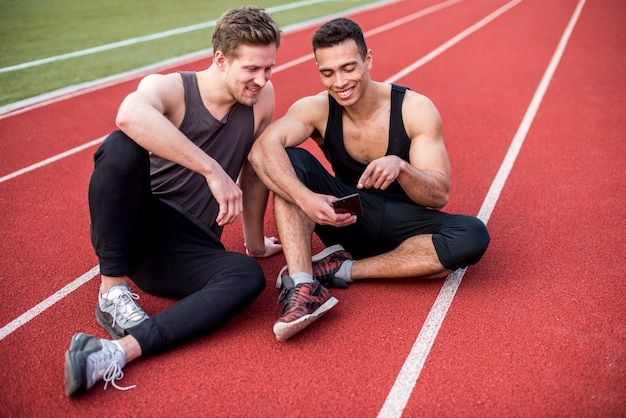 Male athlete showing something on mobile phone to his friends sitting on race track Free Photo