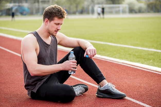 Male athlete sitting on race track holding water bottle in hand Free Photo