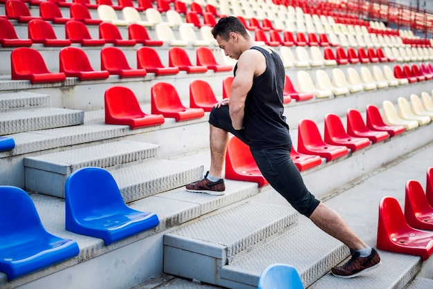 Male athlete stretching his leg on staircase near bleachers Free Photo
