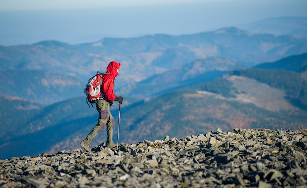 Male backpaker walking on the rocky top of the mountain Premium Photo