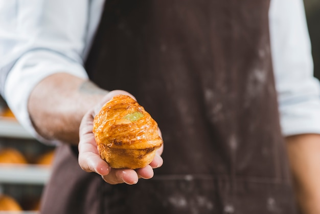 Male baker in apron holding freshly baked sweet puff pastry Free Photo