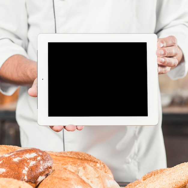 Male baker holding blank digital tablet with baked breads Free Photo