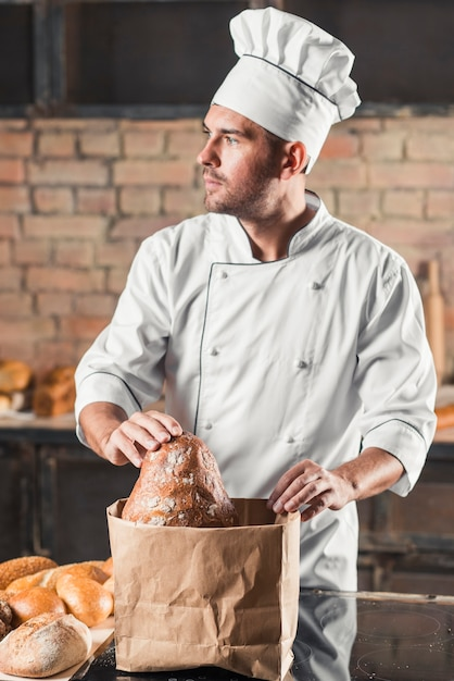Male baker holding bread in the brown paper bag Free Photo