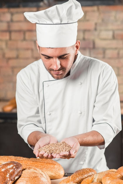 Male baker holding handful of wheat grain with variety of baked breads on table Free Photo