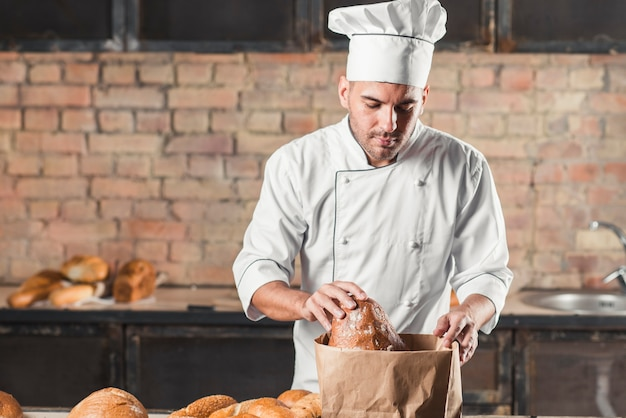 Male baker looking breads in paper bag Free Photo