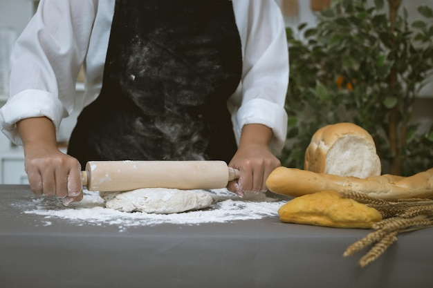 Male baker prepares bread with flour Free Photo