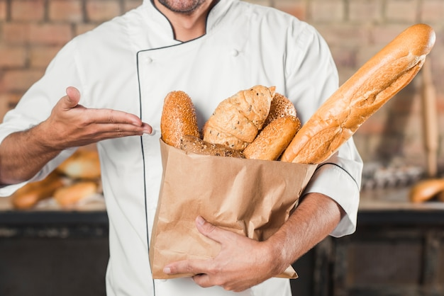 Male baker showing loaf of breads in brown paper bag Free Photo