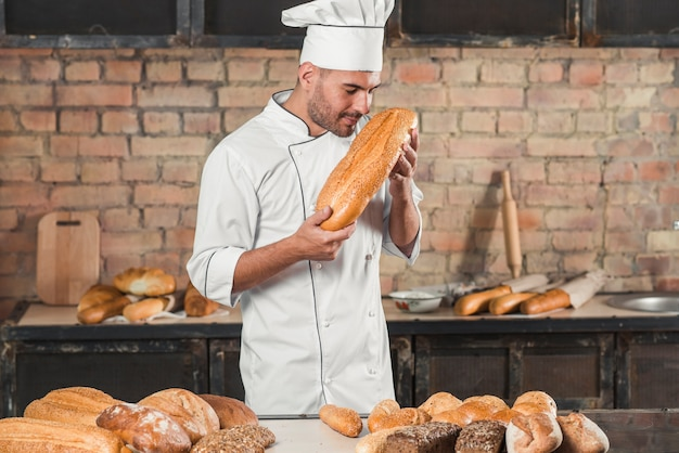 Male baker smelling baked bread loaf Free Photo