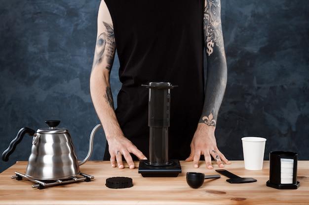 Мужской бариста заваривает кофе. альтернативный метод аэропресс. Бесплатные Фотографии