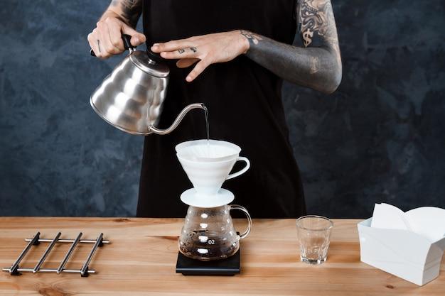 男性のバリスタがコーヒーを淹れています。別の方法を注ぎます。 無料写真