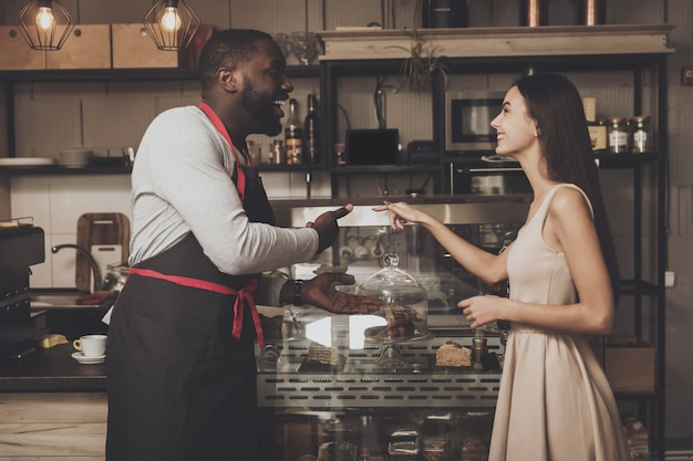 Male barista helps a girl to choose a dessert Premium Photo