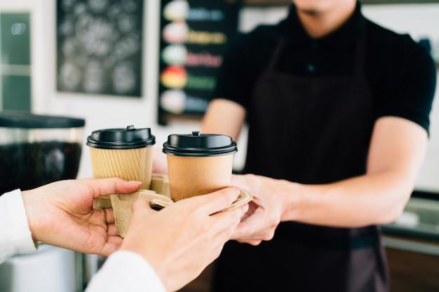 コーヒーショップで持ち帰り用の紙の使い捨てカップでコーヒーを提供する男性のバリスタ。 Premium写真