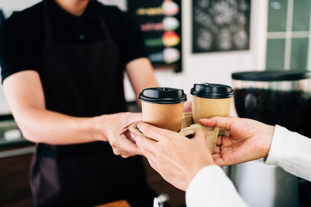 Male barista serving coffee in takeaway paper disposable cups in the coffee shop. Premium Photo