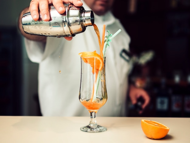Male bartender pouring cocktail from shaker Free Photo