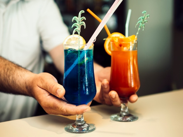 Male bartender serving exotic cocktails Free Photo