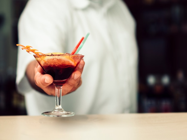 Male bartender serving vibrant drink in martini glass Free Photo