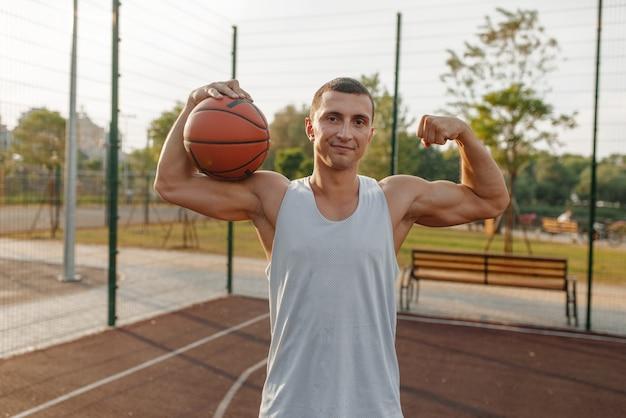 Баскетболист мужского пола с мячом показывает свои мышцы на открытом корте, вид спереди. Premium Фотографии