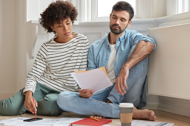 男性のひげを生やした会計士と彼の秘書は、モダンなアパートで一緒に働き、木の床でポーズをとり、財務報告について話し合い、論文を真剣に見つめ、分析を研究し、自宅で快適に感じます 無料写真