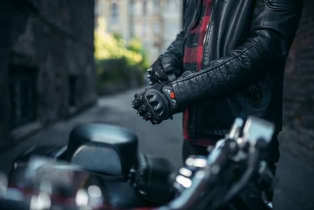 Байкер в кожаной куртке надевает перчатки перед поездкой на классическом чоппере Premium Фотографии
