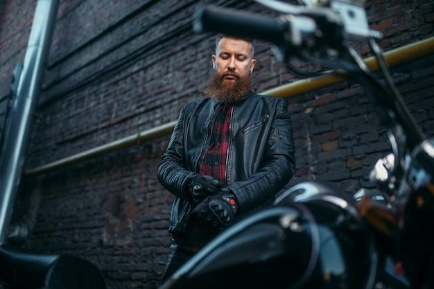 Байкер в кожаной куртке надевает перчатки Premium Фотографии