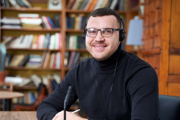 Male blogger streaming from library using laptop and microphone Premium Photo