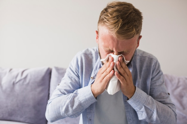Male blowing nose with handkerchief on sofa Free Photo