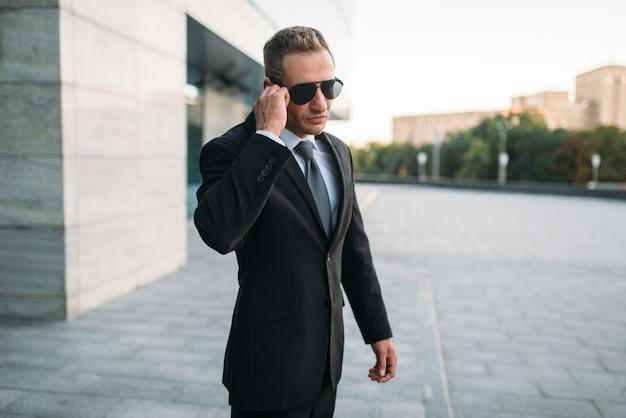 防犯イヤホンで屋外で話しているスーツとサングラスの男性のボディーガード。プロの警備は危険な職業です Premium写真