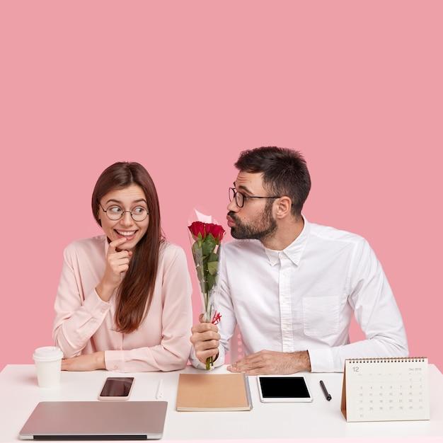 Босс-мужчина влюбился в молодого симпатичного коллегу, дарит красивые красные розы, складывает губы для поцелуя, счастливая дама получает комплимент и цветы, сидит за рабочим столом в офисе у розовой стены Бесплатные Фотографии
