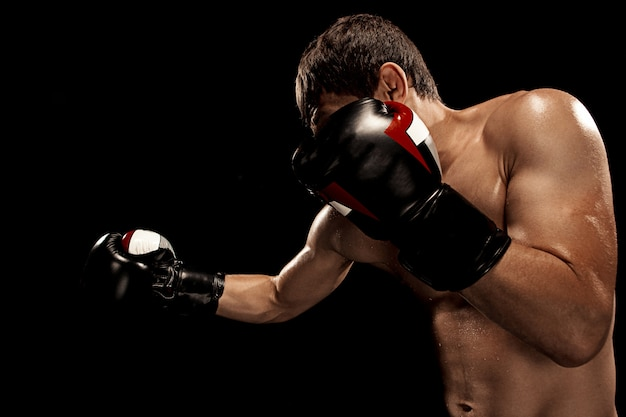 Male boxer boxing in punching bag with dramatic edgy lighting Free Photo