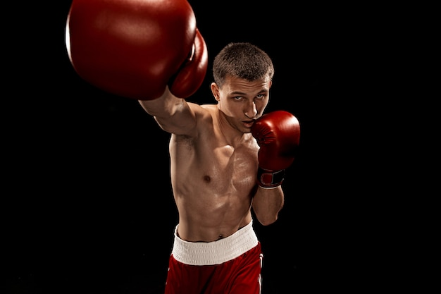 Male boxer boxing with dramatic edgy lighting on black Free Photo