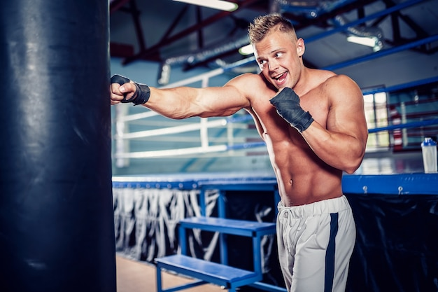 Male boxer training with punching bag in dark sports hall. Premium Photo