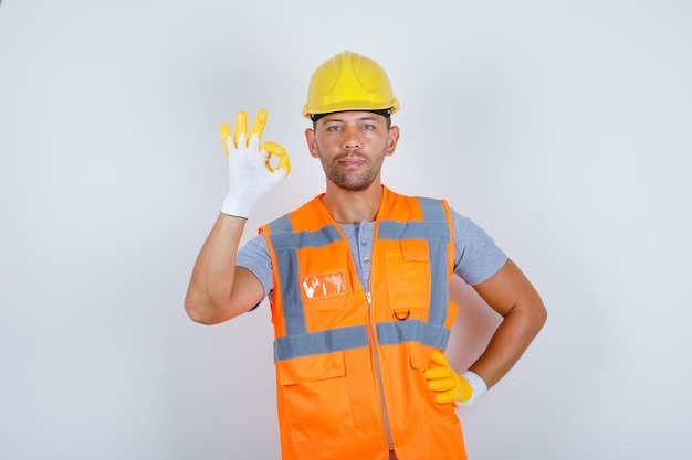 Male builder doing ok gesture with hand on waist in uniform, helmet, gloves, front view. Free Photo