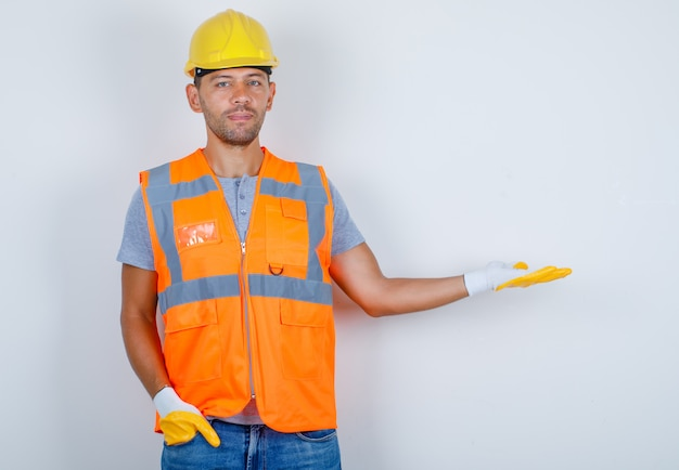 Male builder gesturing as welcoming with hand in pocket in uniform, jeans, helmet, gloves, front view. Free Photo