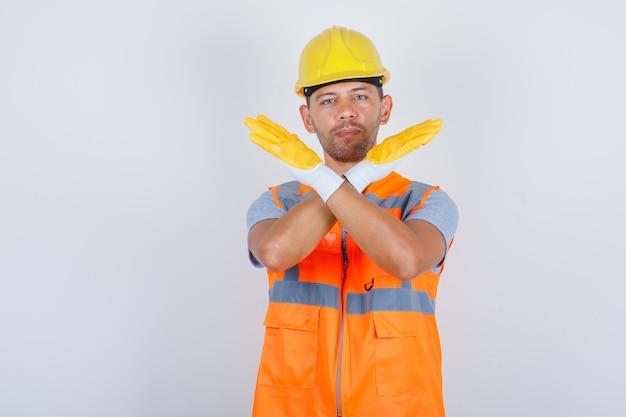 Generatore maschio che non gesturing alcun segno con le braccia incrociate in uniforme, casco, guanti, vista frontale. Foto Gratuite