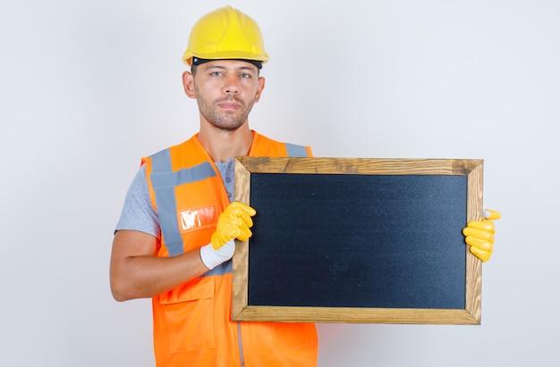 Мужчина-строитель держит доску в форме, шлем, перчатки, вид спереди. Бесплатные Фотографии